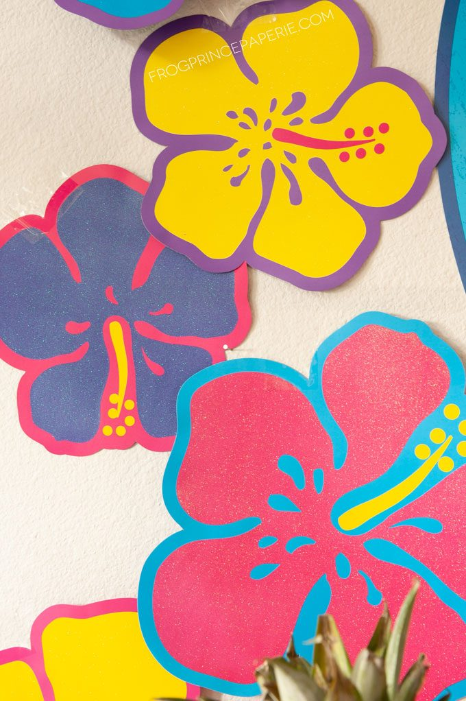 Easy luau party ideas for an easy tiki bar. Purchased hibiscus flowers are bold and colorful as part of the backdrop.