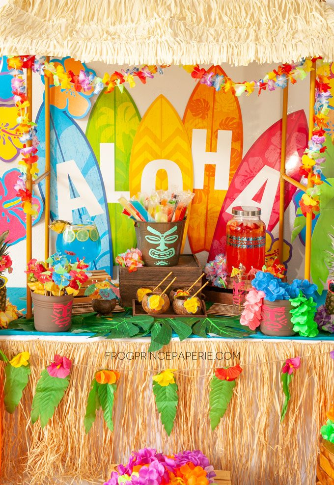 Easy luau party ideas for an easy tiki bar. Purchased surfboard cut outs set a colorful backdrop.