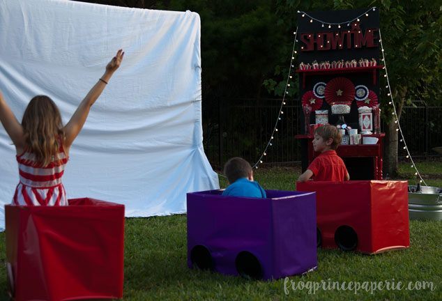 Cardboard boxes turned cars make the perfect viewing area for the kids at a backyard movie party