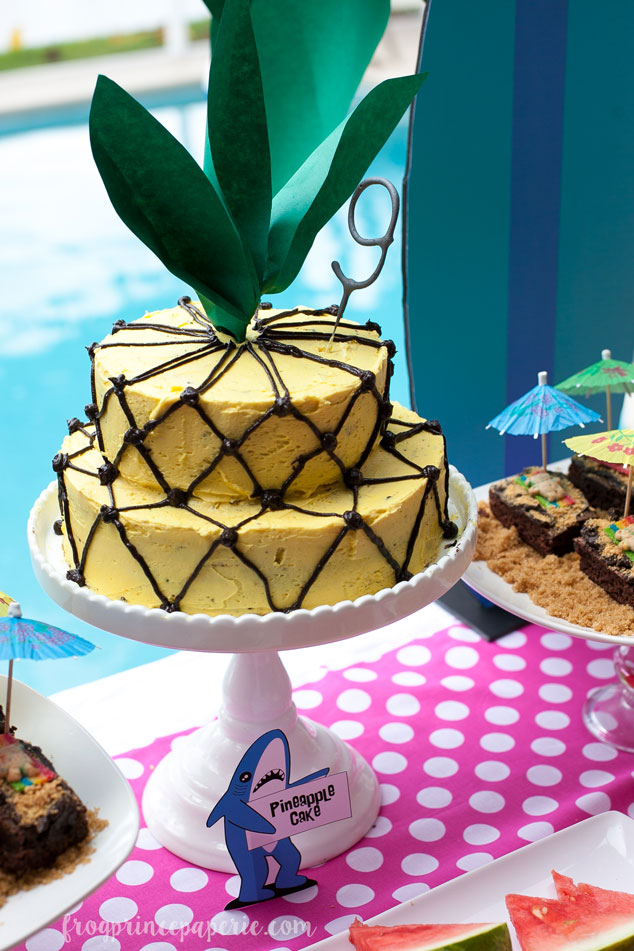 Easy to make DIY pineapple cake: a two layer tiered cake frosted in yellow with chocolate frosting cross-hatch. Add a green paper flourish and you've got yourself a pineapple cake!