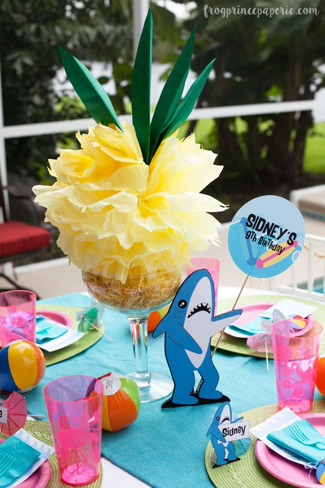 DIY tissue paper pineapples and a helpful sign-holding left shark make for fun pool party centerpieces