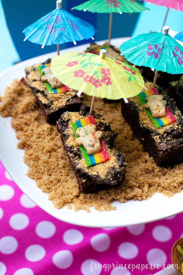 Easy DIY sunbathing bear brownies how-to: Make brownies and cut into rectangles. Sprinkle with crumbled graham crackers. Add a piece of candy tape, a teddy graham, and a paper umbrella and serve up on a bed of brown sugar sand. Perfect pool party food!