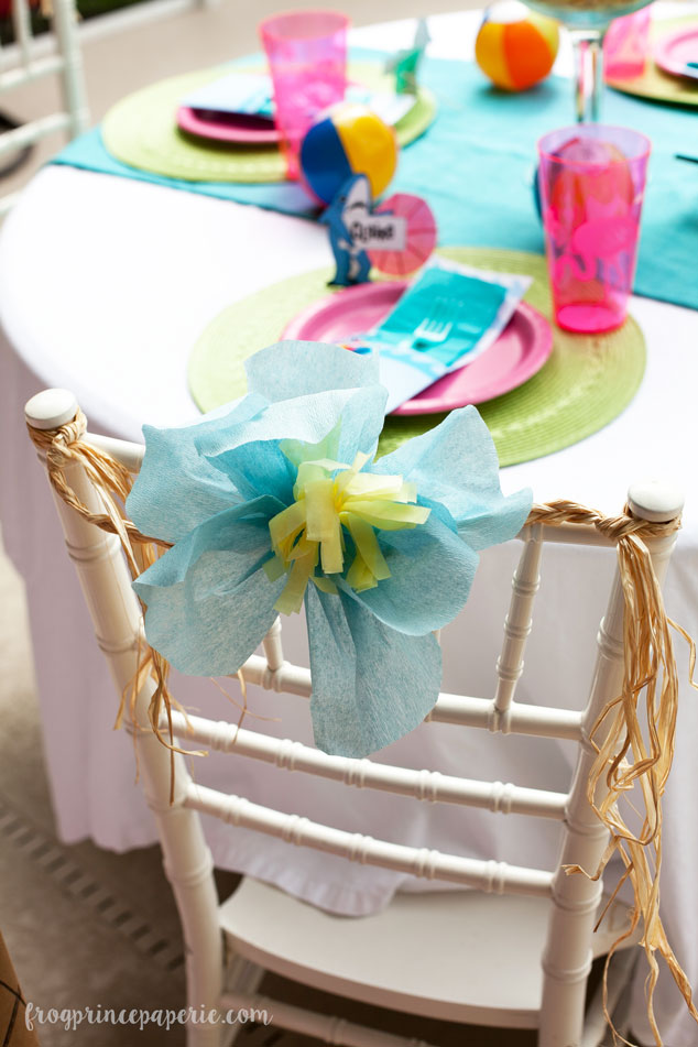 Chair backs are one of my favorite party details! A little raffia and a crepe paper hibiscus flower make a beachy splash for our pool party.